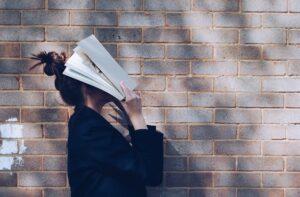 vrouw met boek voor hoofd voor kennis en training contactcenters